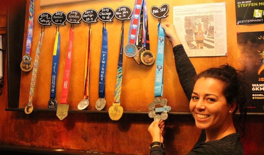 In Speciaal bier café De Pompe hangen ze op een rij, de marathon medailles. Roxanne Machielse hangt haar medaille voor het uitlopen de Big Six marathons er bij. FOTO: Leon Janssens