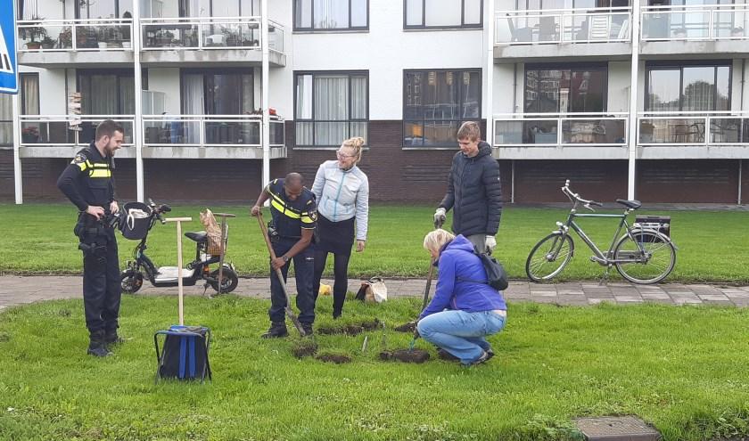 Bij de flats aan De Baan kwam zelfs de politie een handje meehelpen en zette de schop in de grond voor het leuke initiatief van KlimaatNeutraal IJsselstein. (Foto: KNIJ)