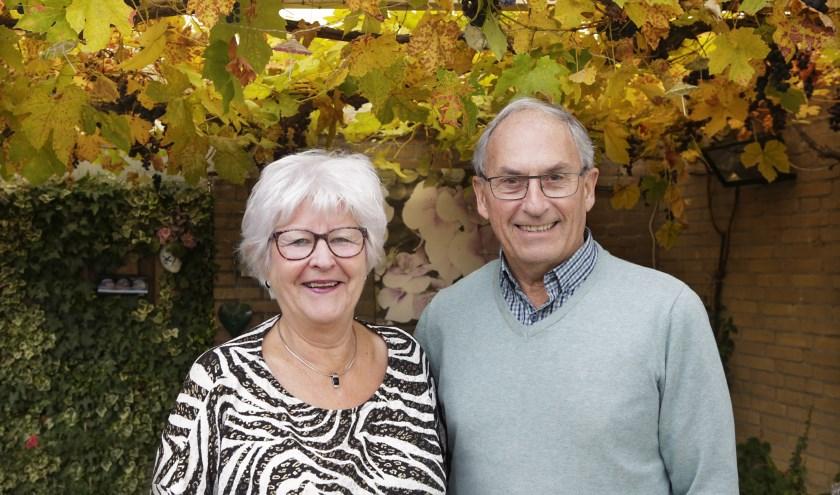 Vol trots poseren Mieke en Louis Veraa voor de wijnrank die jaarlijks voor enkele flessen wijn zorgt. (Foto: Jurgen van Hoof).