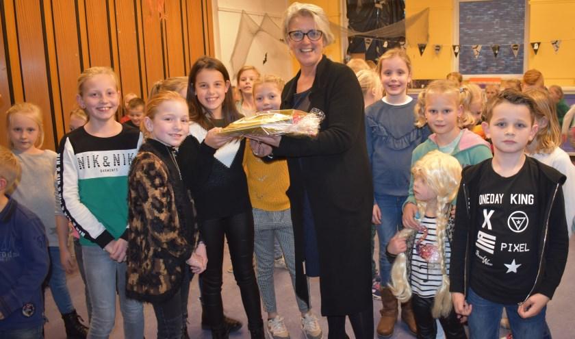 Celeste (groene trui), Maud (met ketting) en Tara (zwart-witte trui) hebben de map aangeboden aan burgemeester Tigchelaar. Foto: Van Gaalen Media.