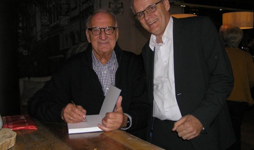 Henk van Baalen (l) signeert het boek voor Vincent Benschop die speciaal voor de presentatie uit Zutphen kwam.