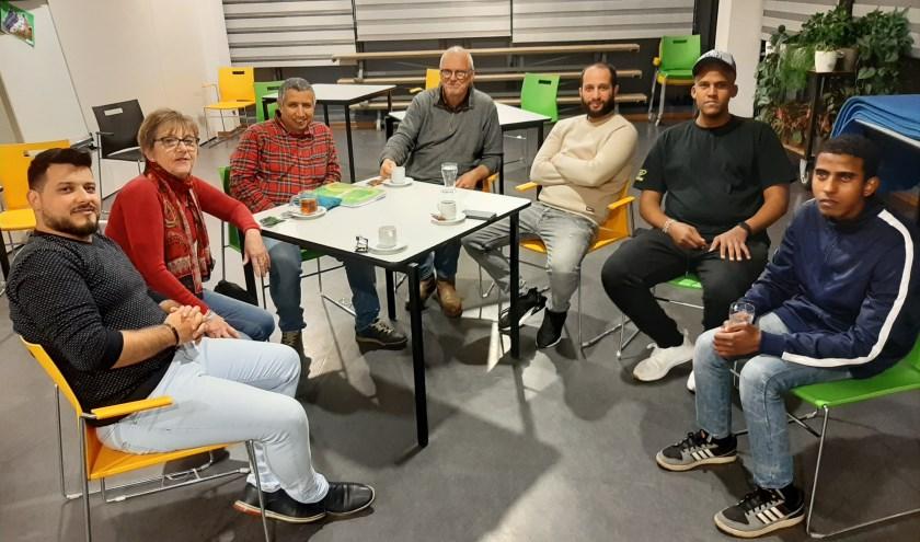 De mannengroep bijeen. Links vrijwilliger Erna en tweede van rechts deelnemer Abdi.