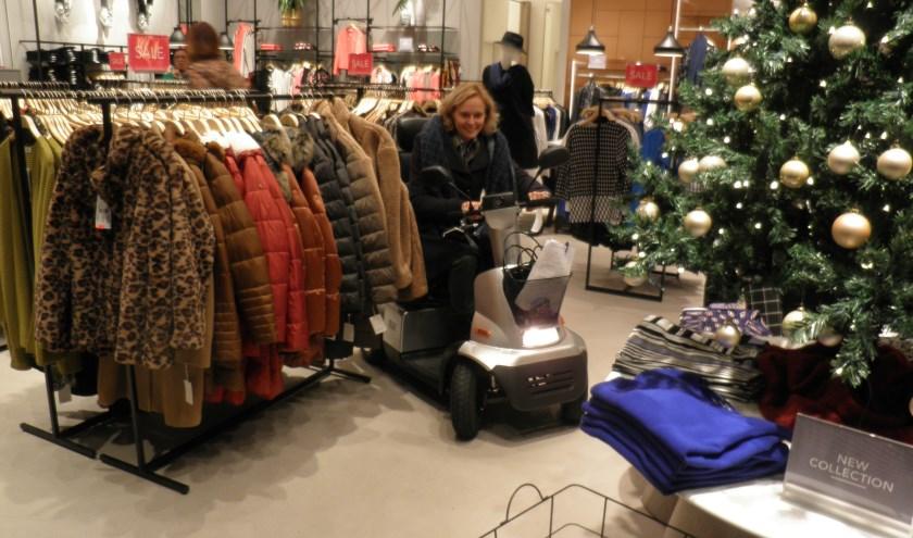 Wethouder Ingeborg ter Laak ervaart hoe het is met een scootmobiel naar kleding voor de feestdagen te zoeken. Foto Kees van Rongen