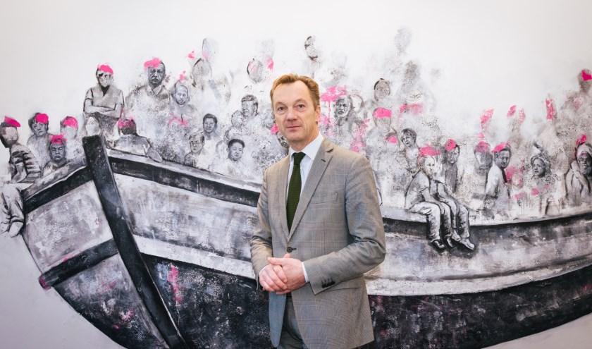 Wim Pijbes op het kantoor van Droom en Daad. Het werk achter hem is in de toekomst te zien in het landverhuizersmuseum op Katendrecht. (Foto: Caro Linares)
