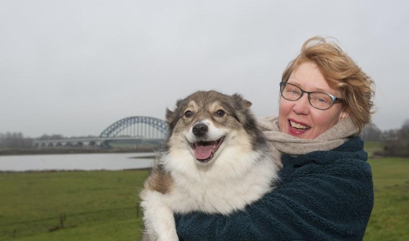 Kunsthistorica en schrijfster Linda Barendse en haar hond Jip maken een wandeling met uitzicht op de IJssel.  (foto: Eva Posthuma)