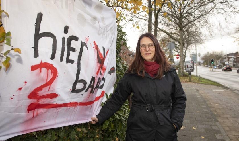 Rita Lange-Stumm voor het spandoek dat zij verfde om aandacht te vragen voor de verkeersoverlast voor haar woning. (foto: Jimmy Israël)