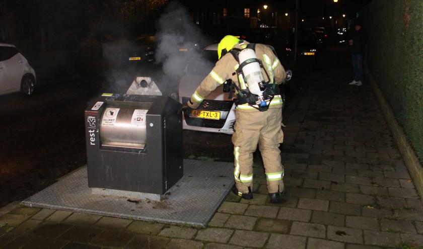 Brandweer druk met containerbrand te blussen.