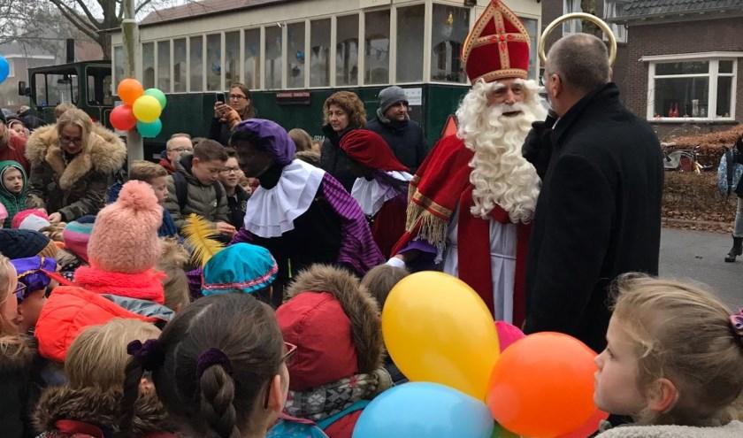 Sint in gesprek met de directeur Tom. Op de achtergrond de tram waarmee Sint de school bezocht.