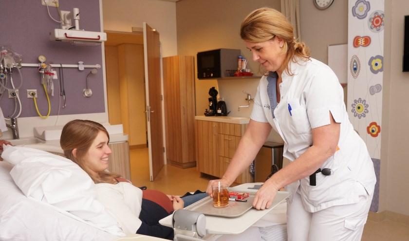 Een verpleegkundige brengt een zwangere een kopje thee op één van de kraamsuites.