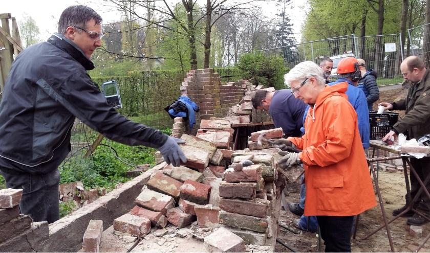Vrijwilligers van het eerste uur nauwgezet aan het werk met de ontmanteling van de historische muur. Momenteel ligt het 'project' volledig op de kont. (foto: gertbudding.nl)