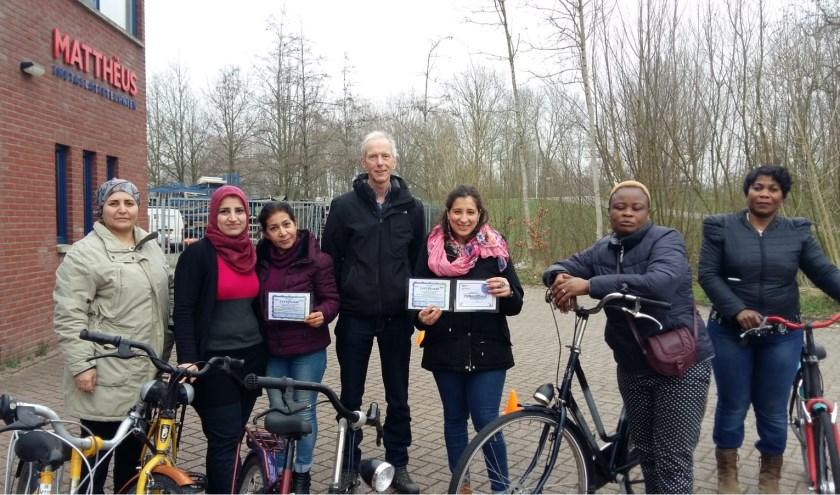 De eerste trotse certificaathouders temidden van andere cursisten en hun fietsdocent.