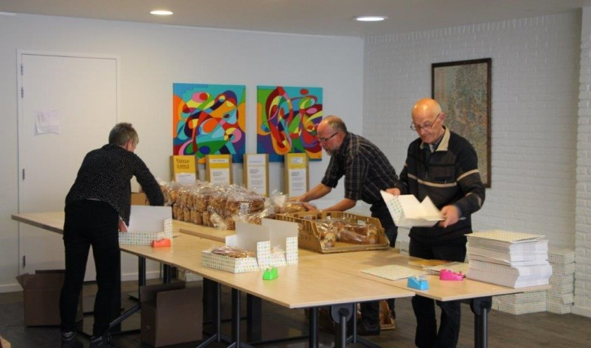 Vrijwilligers zijn druk bezig de ongeveer 650 paasbroden en kaarten in te pakken.