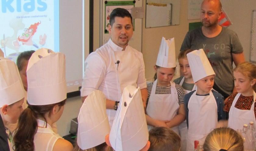 De Helmondse ster-kok Jermain de Rozario vertelde enthousiast over verschillende smaken op basisschool Brandevoort. Foto: Helmy van Dooren.