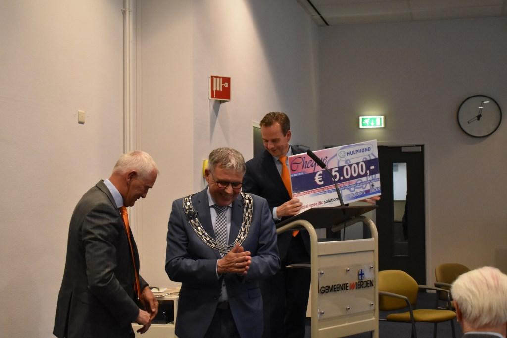PinkRoccade Healthcare, samenwerkingspartner van de gemeente Wierden, heeft een cheque van 5000 euro overhandigd aan de Stichting Hulphond. Foto:  © DPG Media