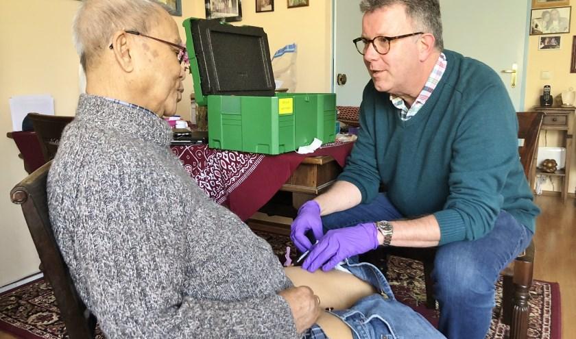 Transmuraal verpleegkundige Rob Verhoef geeft de patiënt thuis de injectie met het middel bortezomib.