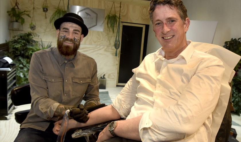 Demian van Subskin Ink tatoeëert de titel van het gedicht 'Ik lijf mijn woorden in' bij stadsdichter Pieter Stroop van Renen. Foto: Marianka Peters