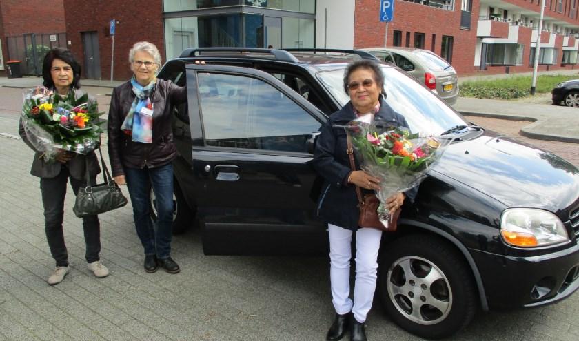 Bloemen voor Ine Akkermans (links) en Lasmi Lans, deelnemers aan de 750e rit van AutoMaatje in Tilburg. In het midden chauffeuse Marianne.