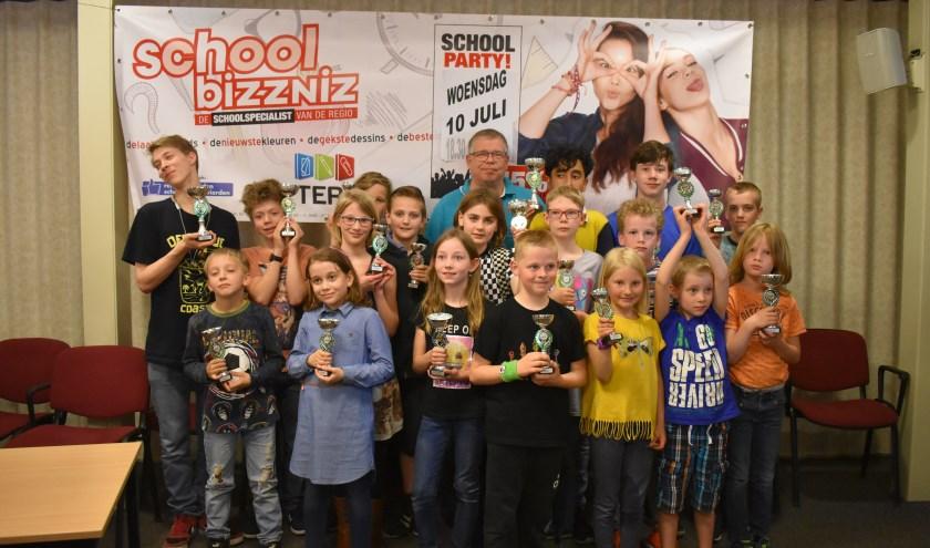 Alle winnaars van het jeugdschaaktoernooi, met op de achtergrond sponsor John Reterink.