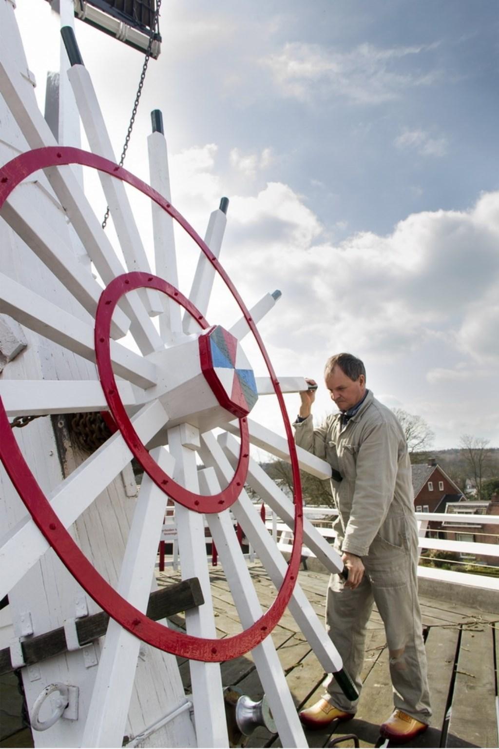 Molenaar Jan van de Beld druk aan het werk bij 'zijn' molen. Foto: Vrienden van de molen © DPG Media
