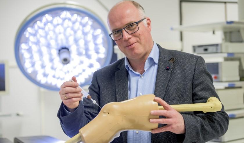 ProfessorMarcel Karperien toont de baanbrekende eenvoudige injectiespuit met hydrogel.