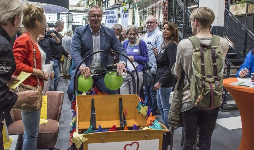 Wethouder Arjan Kampman maakte woensdag 22 mei op de Beursvloer de eerste match door de zaal binnen te fietsen op een versierde bakfiets.