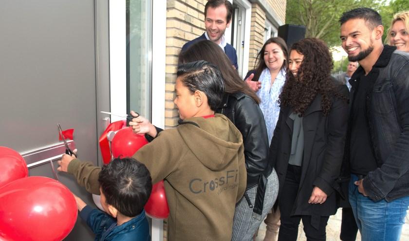 De kinderen van de familie Marlissa 'knippen' hun nieuwe woning open. Rechts directeur Marieke Kolsteeg (Foto Waterweg Wonen).