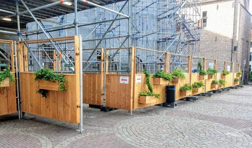 Aan de Groene Bouwhekken voor de gevel van het stadhuis aan het Grote Kerkplein hangen tientallen bloembakken.