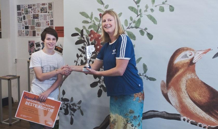 Uit handen van docent Janke Nieboer krijgt Julian van Well de prijs overhandigd.
