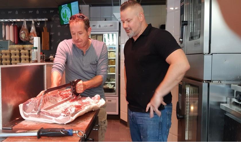 Onze verslaggever Frans Limbertie lijkt geroutineerd de zaag in de lenden van een varken te zetten, terwijl eigenaar Martin van Broekhoven kijkt of het wel helemaal goed gaat.