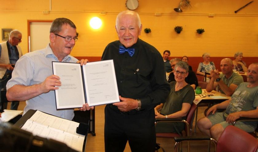 Tijdens het zomerconcert van seniorenkoor 'Ligtklanken' op 23 juni, krijgt Kees van Kampen de Erespeld van de gemeente Veldhoven, uitgereikt door wethouder Hans van de Looij. FOTO: Ad Adriaans.