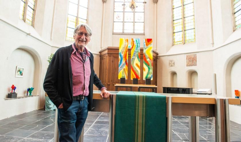 Jan Warnaar tussen zijn glaskunstwerken in de Grote Kerk. Samen met Eline Brontsema exposeert hij hier tot 16 augustus.