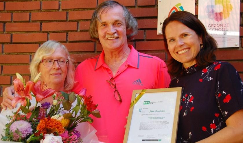 Lia en John Smolders met de oorkonde, overhandigd door Beppie Smit, fractievoorzitter D66 Tilburg.