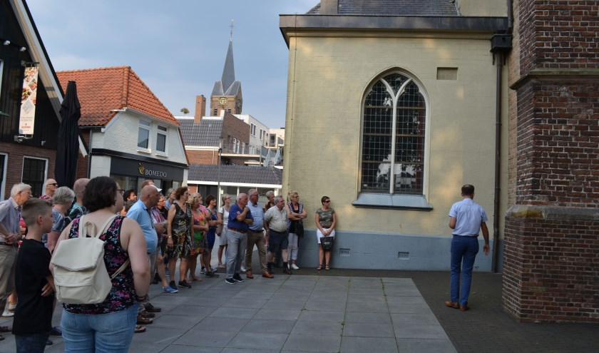Joop Voortman geeft uitleg bij de oudste, tufstenen kerkmuur van de Schildkerk tegenover Brasserie-Uit waar ook de stadswandelingen starten en eindigen. Foto: Jan Joost.