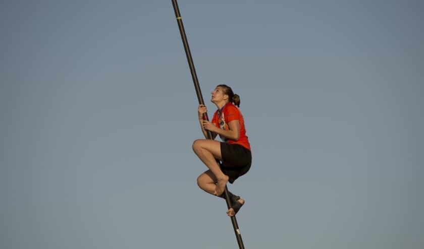 <p>Tijdens een wedstrijd klimt Doriene de Vos hoog in de polsstok.</p>