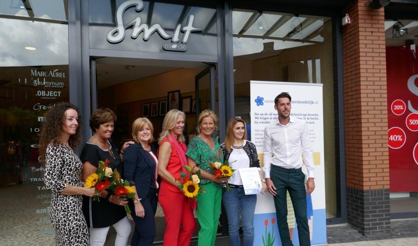 De medewerkers van Smit mode in De Schoof met het door wethouder Steven van Die uitgereikte certificaat.