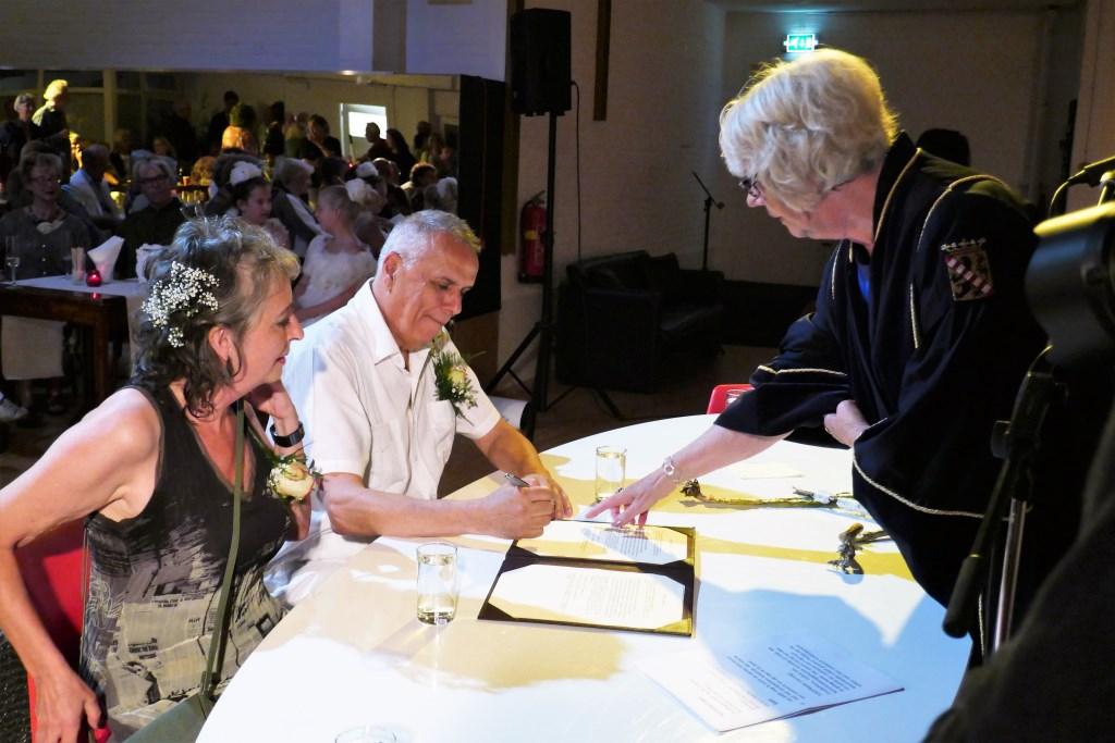 Kathy wijst waar Fred moet tekenen. Petra kijkt instemmend. (Foto: SAGE)  © DPG Media