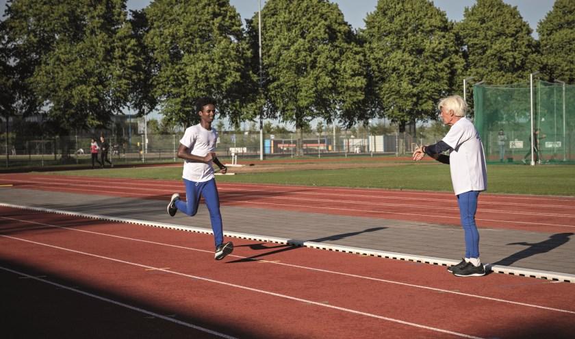 Fotobijschrift: Sportmaatje Cees van ARV Ilion en Samuel trainen samen op de atletiekbaan. Fotograaf: Remco Koers