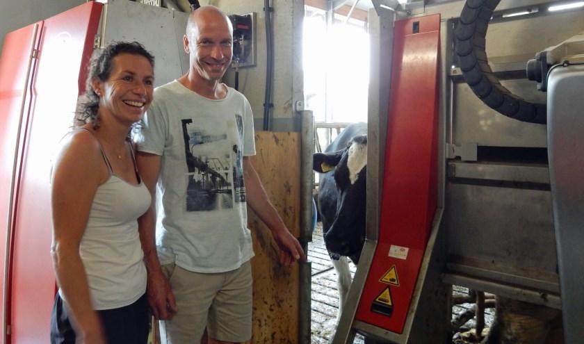 Eva van Zutphen en Reynold van der Grift bij de gloednieuwe melkrobot, die Willie 44 - waarvan de uier rechtsonder zichtbaar is - melkt. Foto: Asta Diepen Stöpler