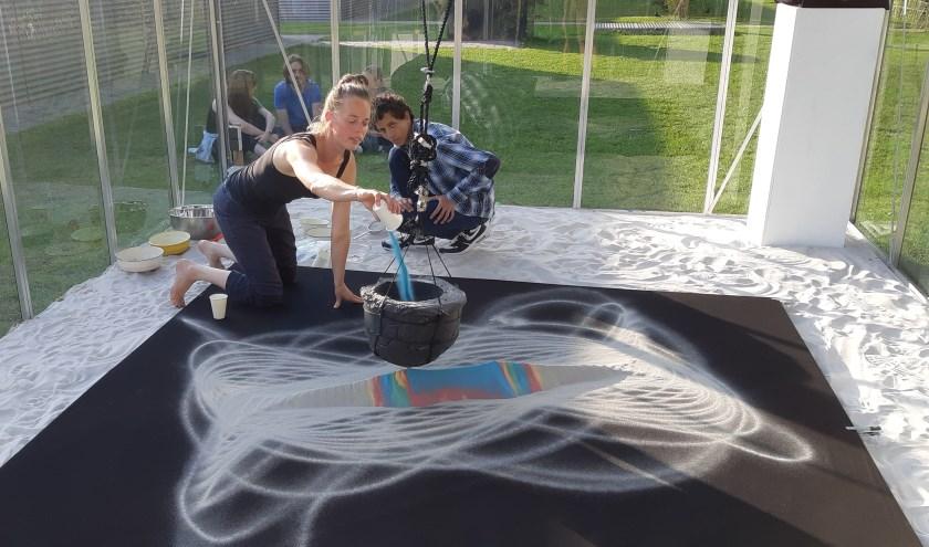 Kunstenares Mariska de Groot bezig met vervaardigen van kunstwerk met pendulum