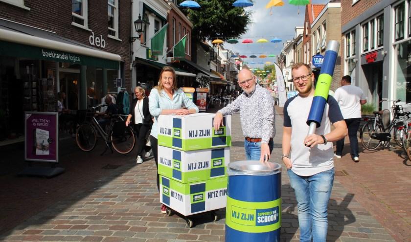 Stefanie Cozijn van RMN zorgt met Frits en Stephan Mulder voor extra afvalbakken en peukenpalen in de winkelstraten. (Foto: Lysette Verwegen)
