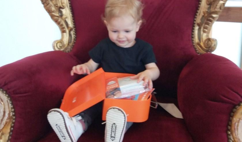 De Kleine Tess van der Voorn pakt nieuwsgierig haar BoekStart-koffertje uit in de bibliotheek. (Foto: Bibliotheek)