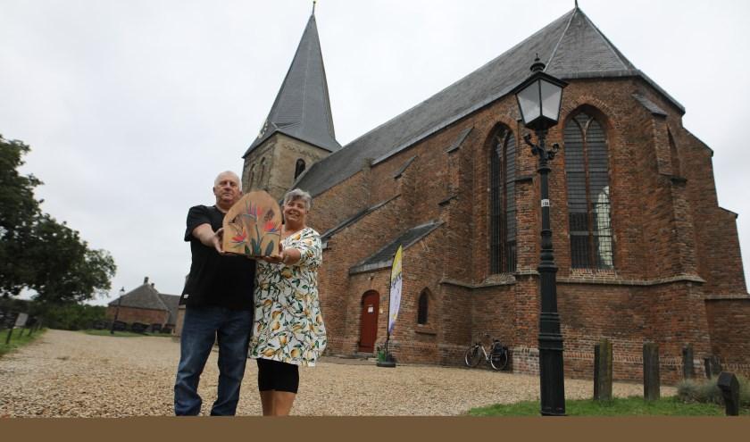 Geert en Marleen voor de duizend jaar oude St Joriskerk. Ze laten een kunstwerk zien dat ze samen maakten. (foto: Feikje Breimer)
