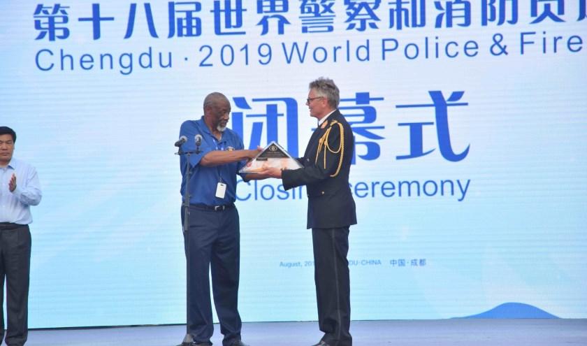 Arjen Littooij, Algemeen Directeur veiligheidsregio Rotterdam-Rijnmond en Bestuurslid WPFG Rotterdam 2021, krijgt de vlag overhandigd door Larry Collins, President WPFG Federation.