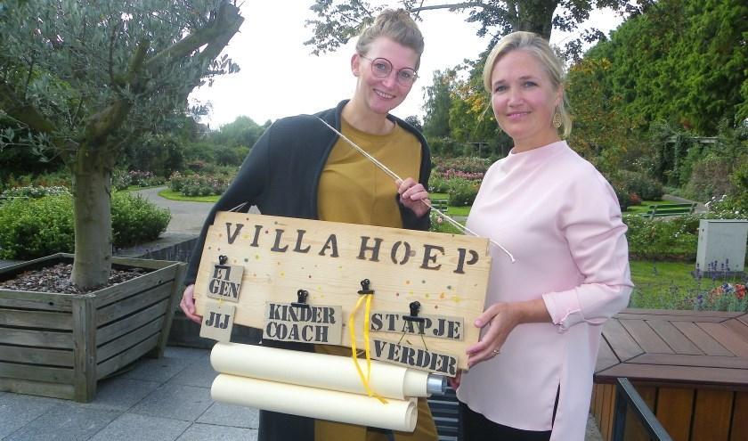 Jantine Schuilenburg (links) en Else Marij Vollebregt met het zelfgemaakte naambord van hun praktijk voor kindercoaching. FOTO's: Morvenna Goudkade