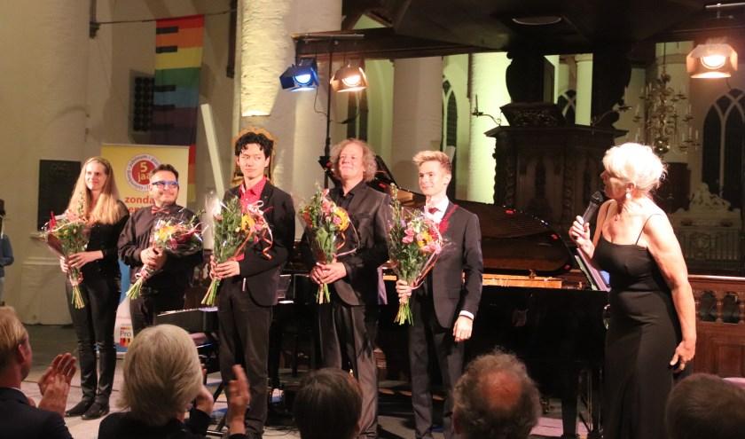 De vijf pianisten werden bij het lustrumconcert door Ellen verhagen in de bloemen gezet.