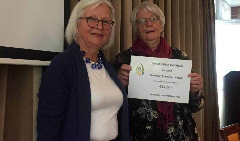 Anda Witsenburg (links) reikt Ans Purmer de cheque uit. Ans Purmer vertegenwoordigd de stichting Lonneker Molen.