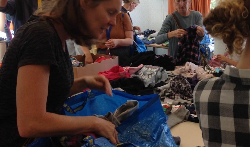 Kopers slaan hun slag op de tweedehands kinderkledingbeurs in Rijkerswoerd