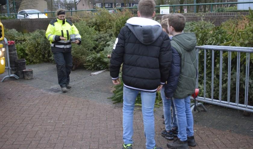 De gemeentewerker telt het geld uit. De jongeren wachten geduldig. Een beeld aan de Componistensingel in Veenendaal-west. (Foto: Pieter Vane)