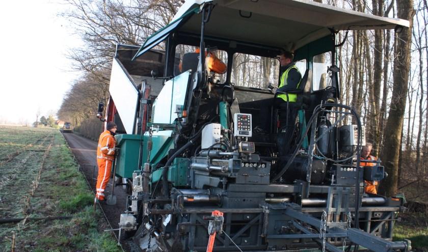 Wethouder Wolbert Meijer zette in 2017 de asfaltmachine in werking voor het fietspad tussen het Oever en de Hoenwaard. (foto: Jan Nitrauw)