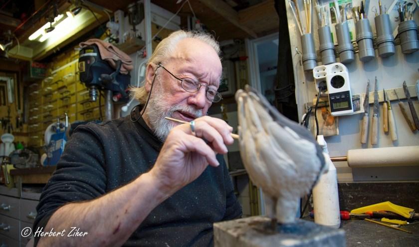 Dick Versluis zoals velen hem kennen: aan het werk in zijn atelier. Fotograaf Herbert Ziher volgde hem in maart tijdens het proces 'Van klomp klei tot vogel'. (Foto: Herbert Ziher)